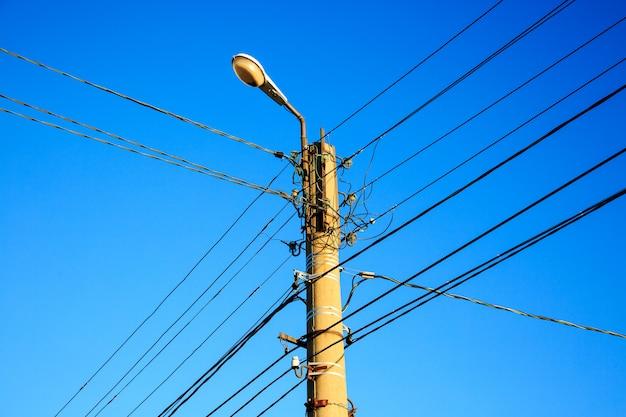 Cable eléctrico y lámpara en poste eléctrico con cielo azul