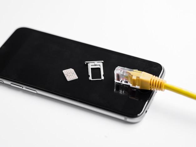 Cable ethernet y tarjeta sim en la parte superior del teléfono