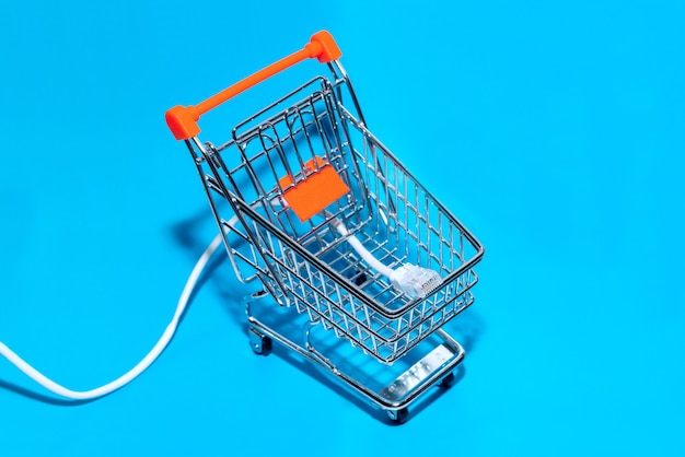 Cable de red en el fondo azul del carro de la compra. vista superior con espacio de copia. enfoque selectivo.