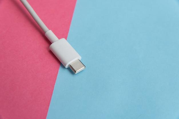 Cable usb tipo c sobre fondo rosa y azul