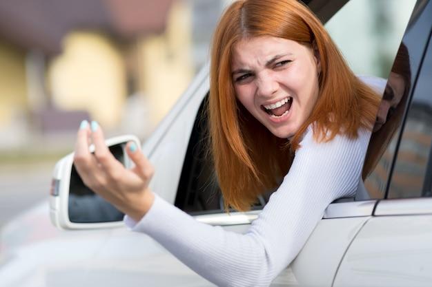 Cabreado, enojado, enojado, agresivo, mujer que conducía un automóvil gritándole a alguien con un gesto con el dedo medio.