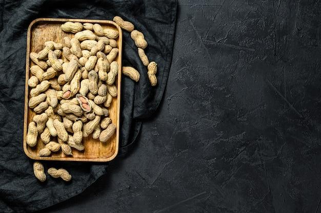 Cacahuetes con cáscara. maní crudo orgánico. fondo negro. vista superior. espacio para texto