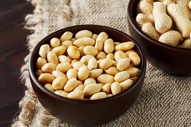 Cacahuetes con cáscara y primer plano pelado en tazas, cacahuetes tostados en sus cáscaras y pelados contra una tela marrón