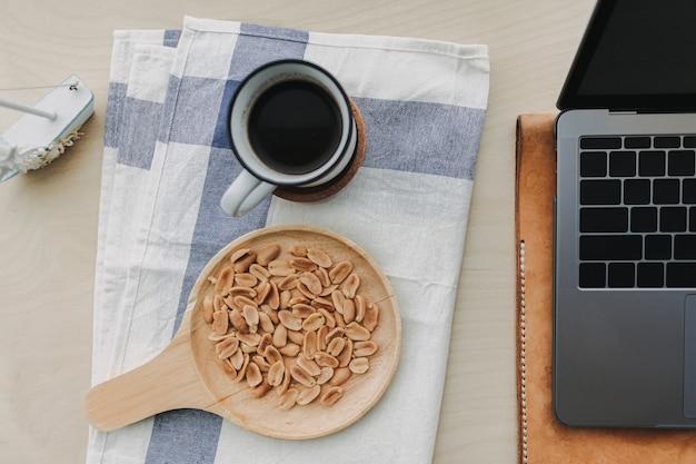 Cacahuetes salados, café negro y portátil en el escritorio