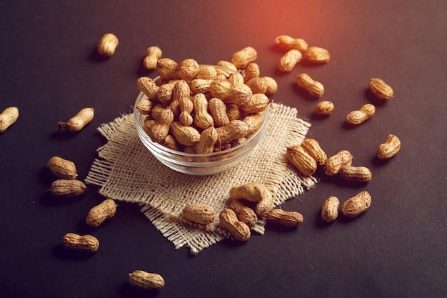 Cacahuetes en un tazón sobre el fondo oscuro.