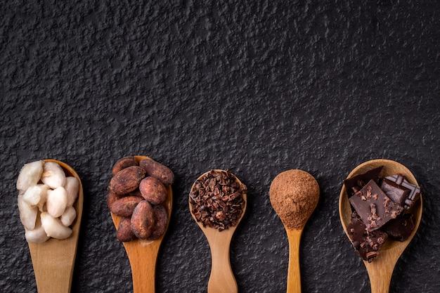 Cacao y chocolate negro en cucharas de madera sobre fondo de madera