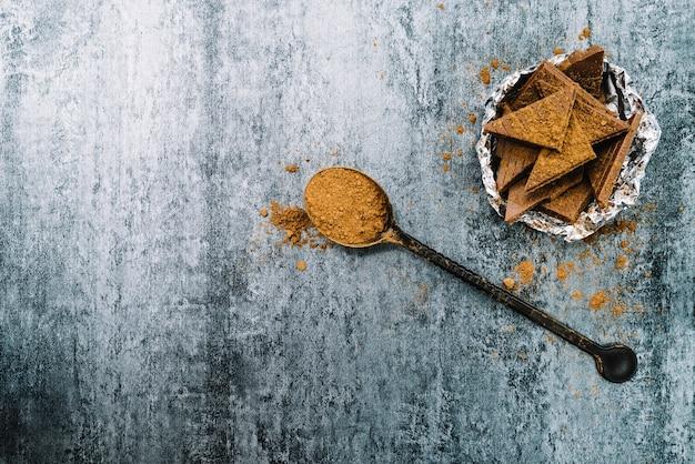 Cacao en polvo y trozos de chocolate en un tazón sobre fondo de hormigón viejo