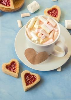 Cacao con malvaviscos y un corazón de galleta. enfoque selectivo