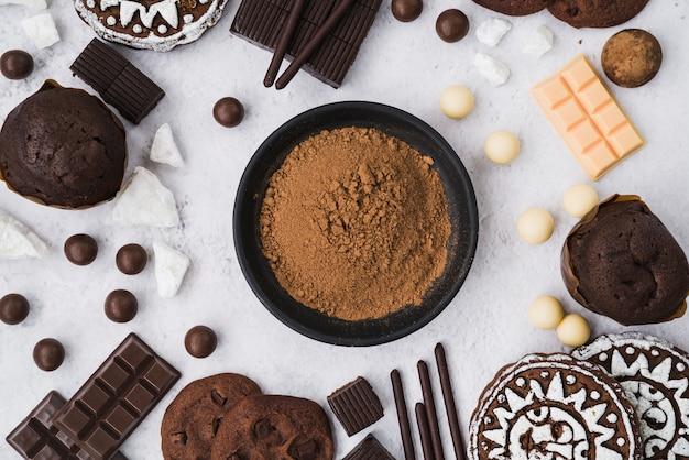 Cacao en polvo con artículos de chocolate sobre fondo blanco