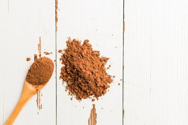 Cacao en polvo derramado cuchara de madera