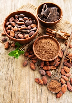 Cacao en polvo natural, chocolate y granos de cacao sobre un fondo de madera