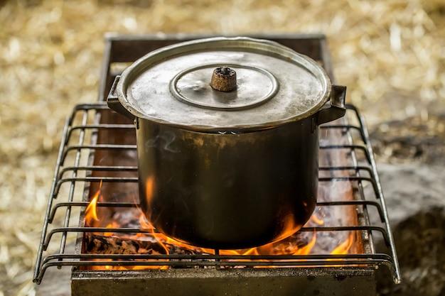 Cacerola al fuego, el concepto de camping y recreación.