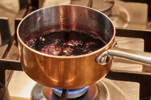 Cacerola de cobre a fuego lento en la estufa para hacer salsa.