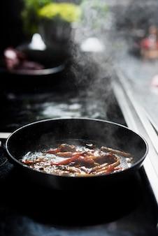 Cacerola con verduras fritas en estufa