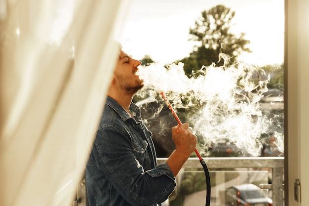 Cachimba de fumar joven guapo en un balcón