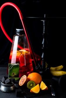 Cachimba roja con rodaja de naranja sobre un fondo negro