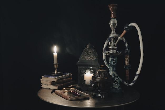 Cachimba shisha junto con libro con velas. concepto de shisha.