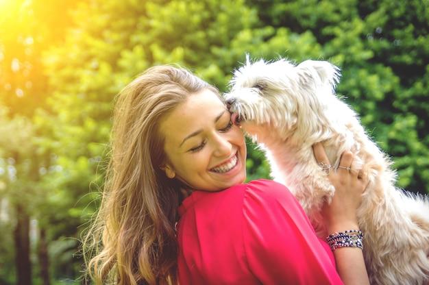 Cachorro perro blanco lamiendo su dueño. atractiva chica caucásica divirtiéndose con su perro