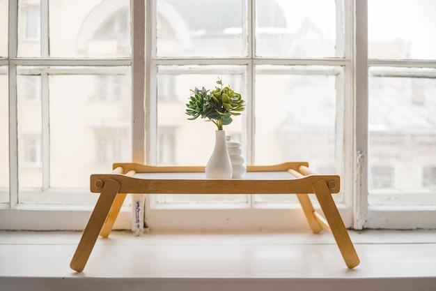 Cactus verde, suculentas en el alféizar de la mesa de madera