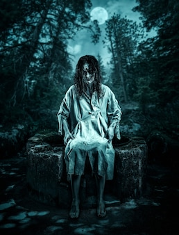 Cadáver aterrador sentado en el pozo en el bosque de la noche. víspera de todos los santos.