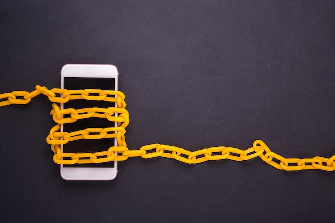 Cadena amarilla bloqueada alrededor del teléfono inteligente