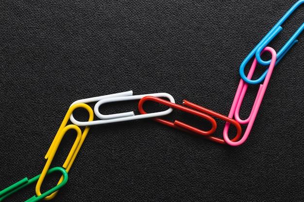 Cadena de clips de papel sobre fondo negro, el trabajo en equipo y el concepto de éxito.