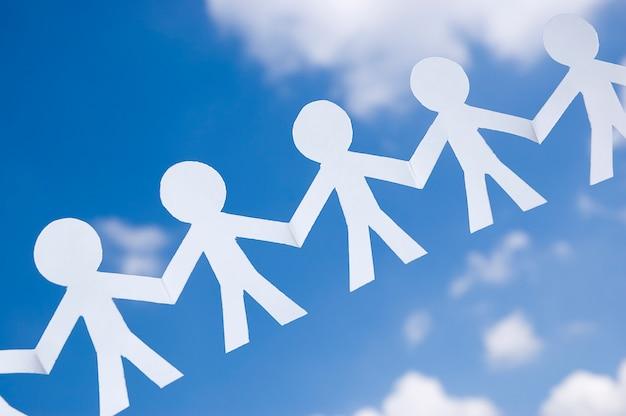 Cadena de hombre de papel en el cielo azul con nubes blancas. símbolo de unidad, hermandad y trabajo en equipo.