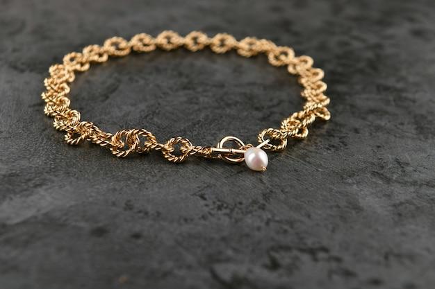 Cadena de oro con perlas sobre mármol.