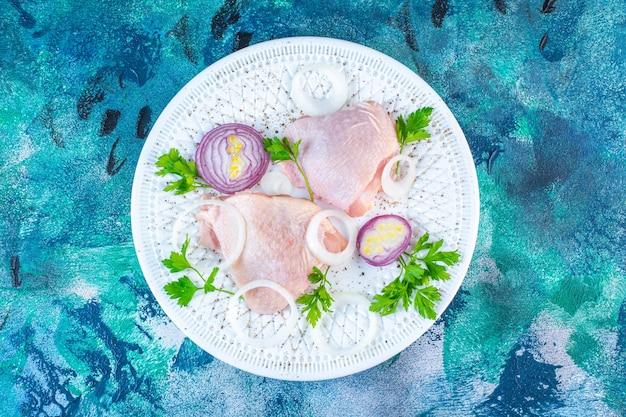 Cadera de pollo crudo con aros de cebolla y perejil en un plato