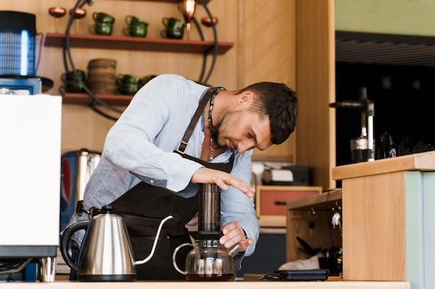 Café aeropress: el barista presiona el dispositivo y las gotas de café se vierten a través del aeropress en la olla