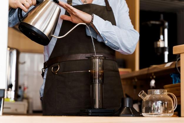 El café aeropress es un método alternativo para hacer café por un barista en la cafetería.