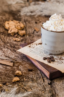 Café de alto ángulo con leche y crema batida con galleta