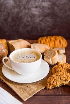 Café alto ángulo rodeado de galletas.