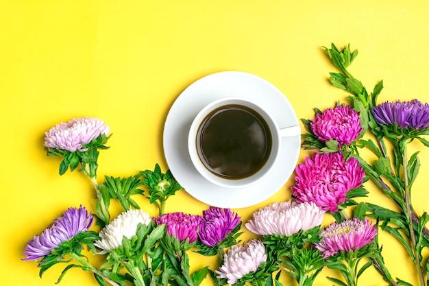 Café americano americano en taza blanca y flores asters sobre fondo amarillo endecha plana