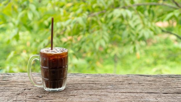 Café americano helado en una mesa de madera y naturaleza verde