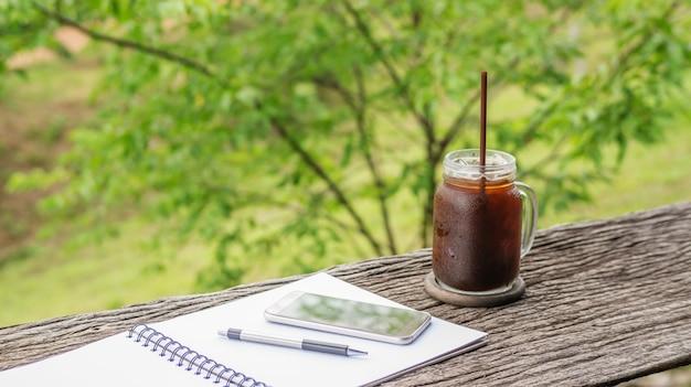 Café americano helado, teléfono inteligente, una pluma y un libro sobre una mesa de madera.