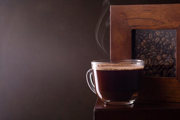 Café aromático fresco en una taza de café y granos de café sobre la mesa.