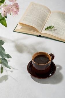 Café aromático fresco en una taza sobre una mesa blanca. fondo claro.