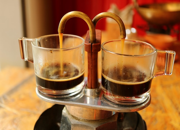 Café aromático que gotea de la mini olla de elaboración de cerveza retro en un par de tazas de vidrio para cavitar