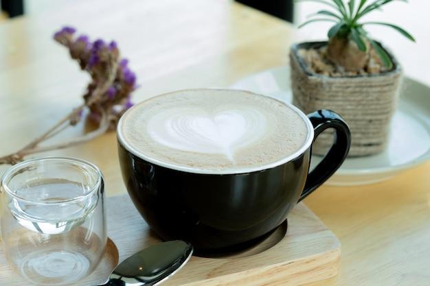 Café del arte del latte en el tiempo de mañana con luz del sol en fondo de madera de la tabla en la cafetería.