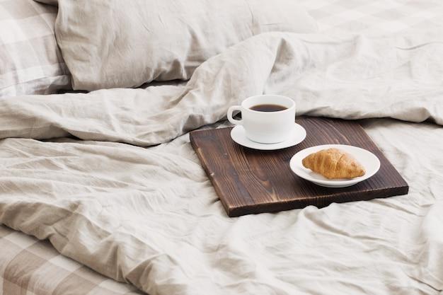 Café en bandeja en la cama en dormitorio