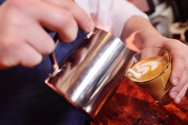 Café barman prepara café con un patrón en la espuma o latte-art