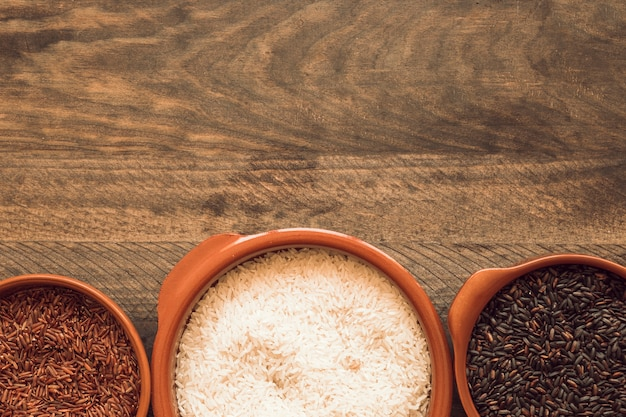 Cafe blanco; tazón de arroz rojo y negro sobre fondo de madera