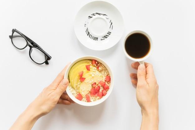 Café y bol con frutas y cereales.
