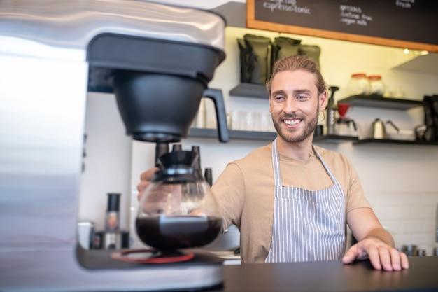 Café, café. sonriente joven adulto en delantal con cafetera cerca de la cafetera detrás del mostrador en la cafetería