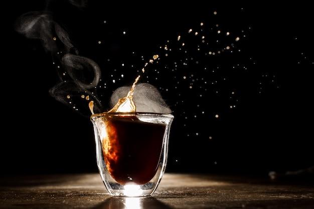 Café caliente y aromático derramado de una taza de vidrio