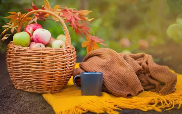 Café caliente y canasta con manzanas sobre una manta amarilla