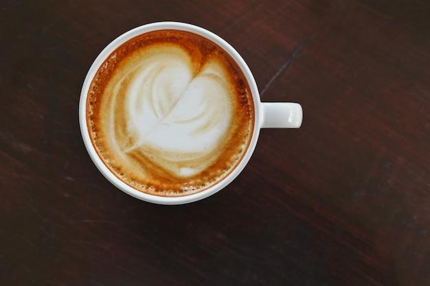 Café caliente cappuccino o café con leche vista superior mesa woodwn con trazado de recorte en la taza de café