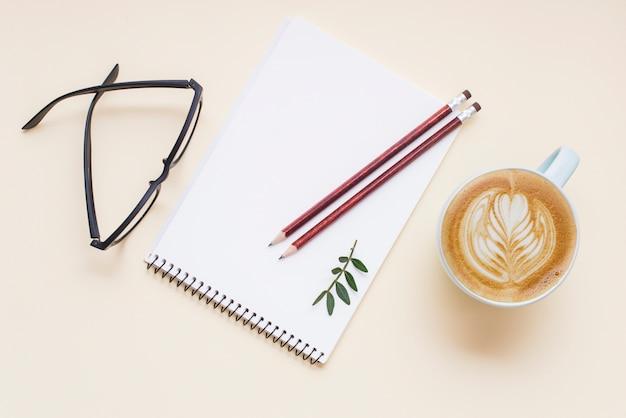 Café caliente capuchino latte art; lentes y lápices en bloc de notas espiral blanco