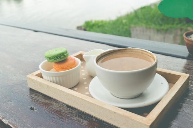 Café caliente para el desayuno con macarrones frescos en una cafetería al aire libre en la panadería